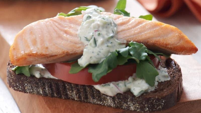 Sándwiches de salmón abiertos con salsa de pepinos y hierbas